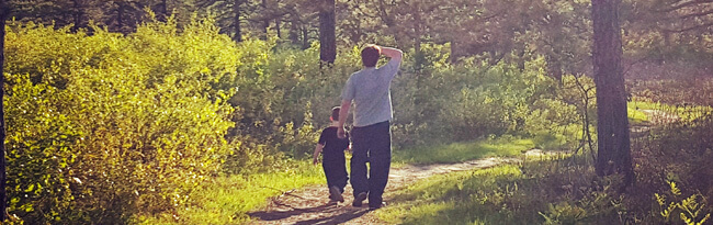 A young boy and adult man walk down a sunny trail in the preserve.
